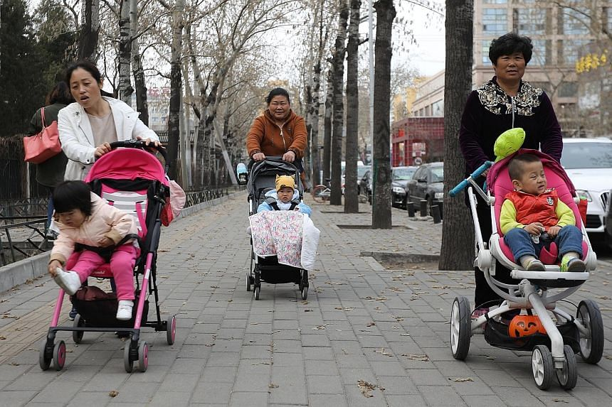 Carers out with their young charges near Beijing's Ritan Park yesterday. China is working to build an environment conducive to child-bearing and child-rearing.