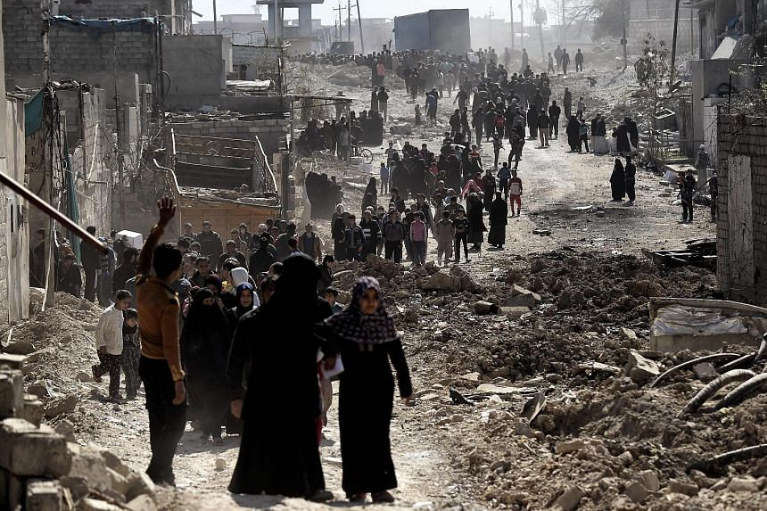 People in west Mosul after a food distribution exercise by Iraqi troops on Friday. As Iraqi forces closed in on terror group ISIS' last urban stronghold in the country, residents were forced to hide in their homes and get by on whatever they had mana