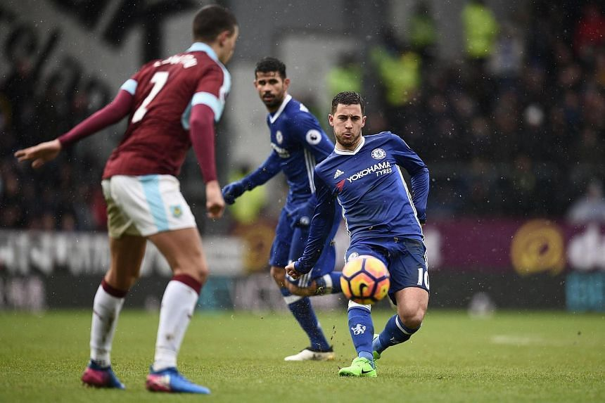 Chelsea's Belgian midfielder Eden Hazard (right) passing the ball during the English Premier League football match between Burnley and Chelsea at Turf Moor in Burnley, England.
