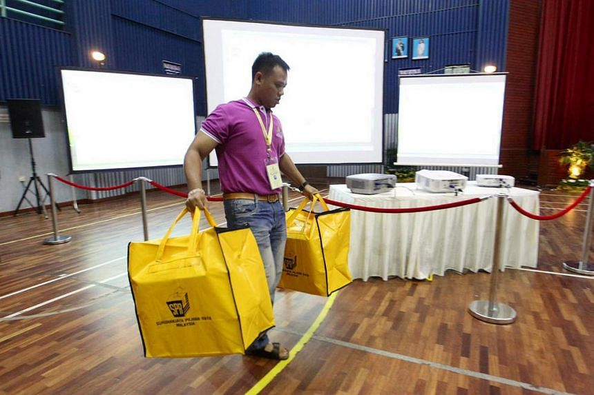 An election official carrying ballot boxes into a multi-purpose hall in Skudai, Johor, on 5 May 2013, the polling day for Malaysia General Elections.