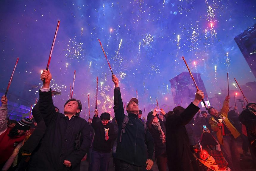 South Korean demonstrators shoot off firecrackers to celebrate the impeachment of Ms Park Geun-Hye during a candlelit rally demanding her arrest.