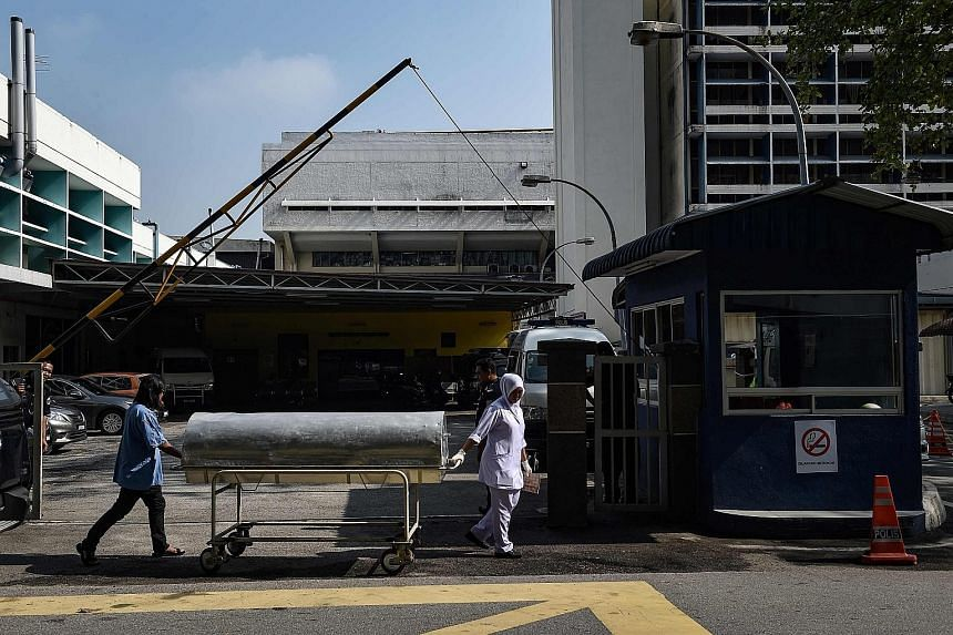 Hospital workers moving a body cart yesterday from Kuala Lumpur Hospital, where the body of Mr Kim Jong Nam lies. Malaysia said last Friday that it had positively identified Mr Kim's body.