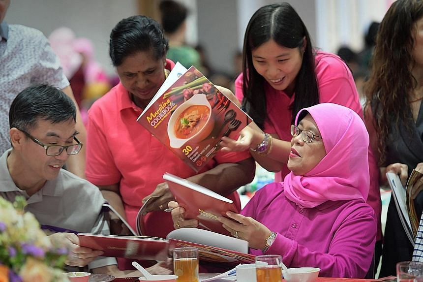 Madam Halimah signing copies of the Marsiling Cookbook at the International Women's Day celebration at Marsiling Community Club yesterday. The book, which has more than 30 recipes, including one by her, raised $26,000 for the Marsiling Independent Mu