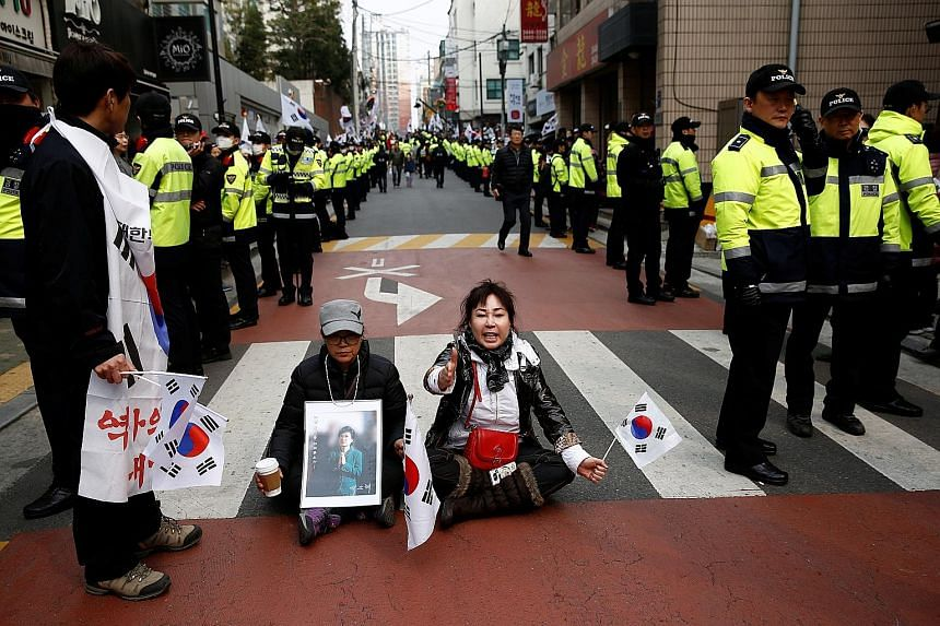 Ms Park's supporters staging a sit-in outside her private home in Seoul to block a media vehicle while awaiting her arrival yesterday. Mr Moon received the highest approval rating among a group of presidential hopefuls, according to a weekend poll. H