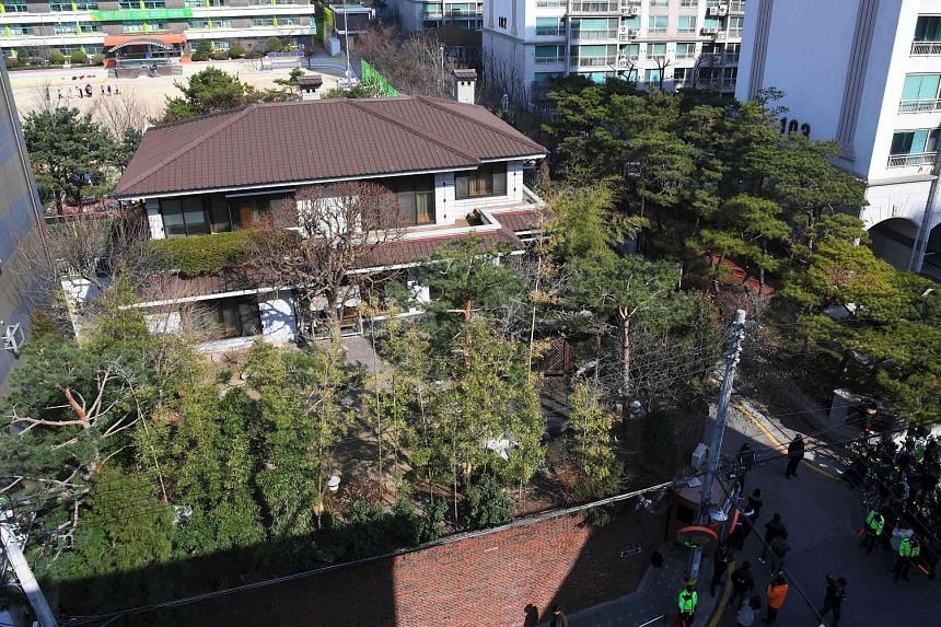 Ms Park (above, centre) arriving at her private residence (left) in the upscale Gangnam district in southern Seoul yesterday. In the public's first glimpse of her since her impeachment, she greeted former aides and political allies in front of her ho