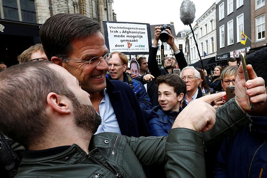 The latest polls show Prime Minister Mark Rutte's party slightly ahead for Wednesday's general election. A supporter snapping a selfie with far-right populist Geert Wilders, who wants to take the Netherlands out of the EU, ban immigrants from Muslim