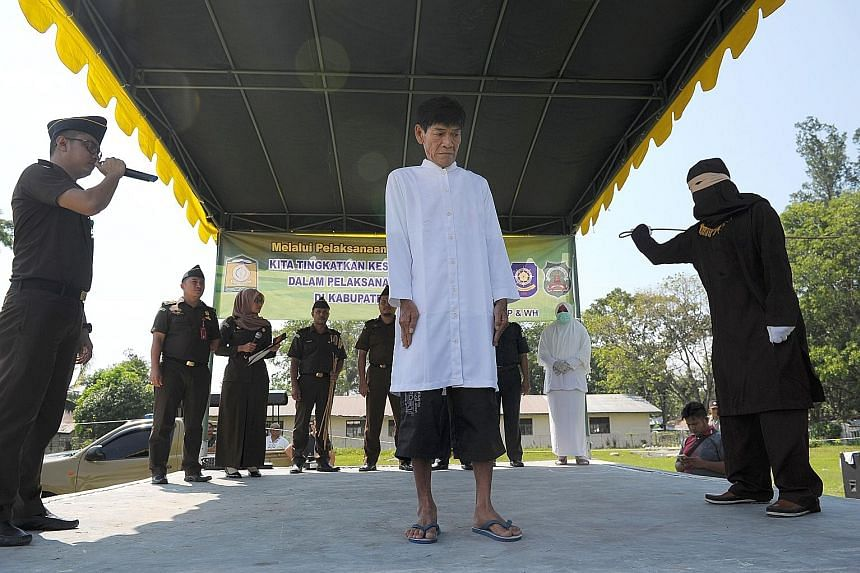 A Buddhist man being caned on Friday, watched by officials. Aceh has been able to cane non-Muslim offenders since 2015 after overhauling its regulations.