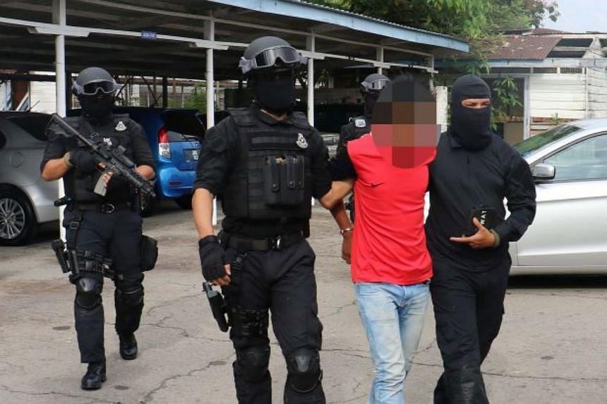 Malaysia's Special Branch Counter Terrorism Division officers detaining one of the seven suspects.