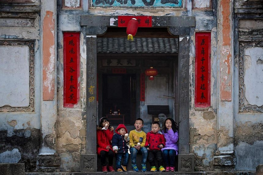 Children eat ice cream as they await a dragon parade in Peitian village, Liancheng county, in China's eastern Fujian province.