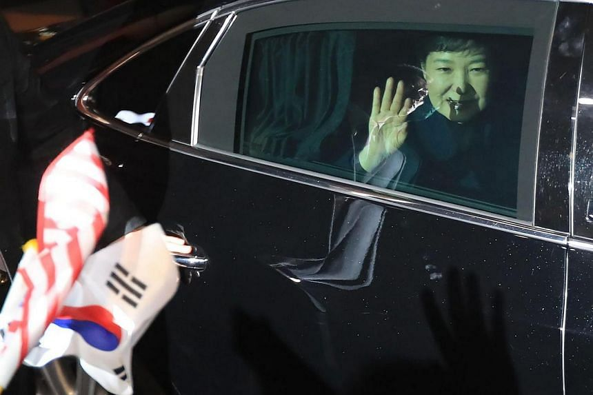 South Korea's impeached ex-president Park Geun Hye waving in a car as she arrives at her private residence in Seoul, on March 12, 2017.
