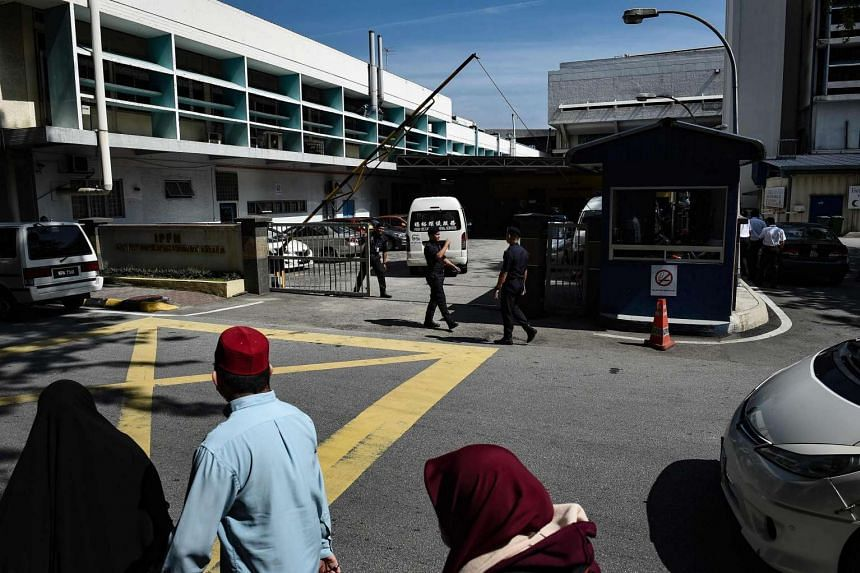 People walking past as Royal Malaysian policemen guard the forensics wing of the Hospital Kuala Lumpur, where the body of Kim Jong Nam lies, in Kuala Lumpur, on March 13, 2017.