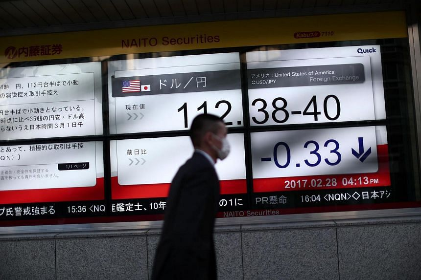 A man walks past an electric quotation board flashing the Nikkei key index of the Tokyo Stock Exchange in Tokyo on Feb 28, 2017.