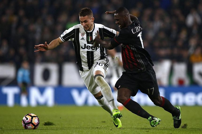 Juventus' midfielder Marko Pjaca from Croa (left) fights for the ball with AC Milan's defender Cristian Zapata  during their Italian Serie A football match, on March 10, 2017.