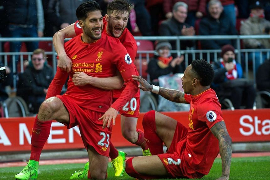 Liverpool's Emre Can (left) celebrates scoring 2-1 lead with teammates.