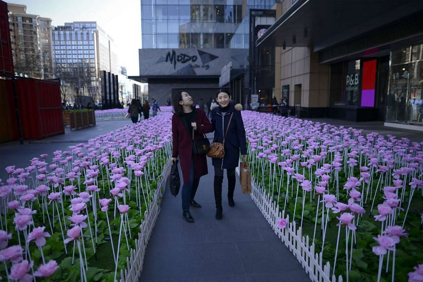 Two women walk past artificial flowers at the entrance of a mall in Beijing on March 8, 2017.