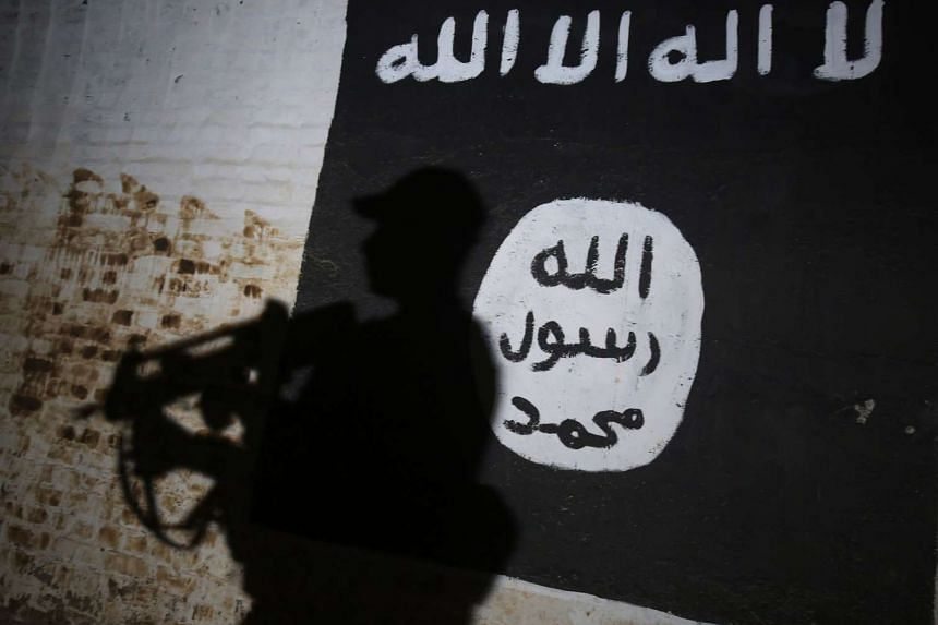 An Iraqi soldier walks past a mural bearing the logo of ISIS  in a tunnel that was used by the terror group near Mosul.
