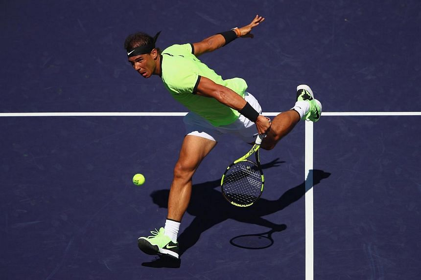 Rafael Nadal plays a backhand volley against Guido Pella of Argentina in their second round match at the BNP Paribas Open.