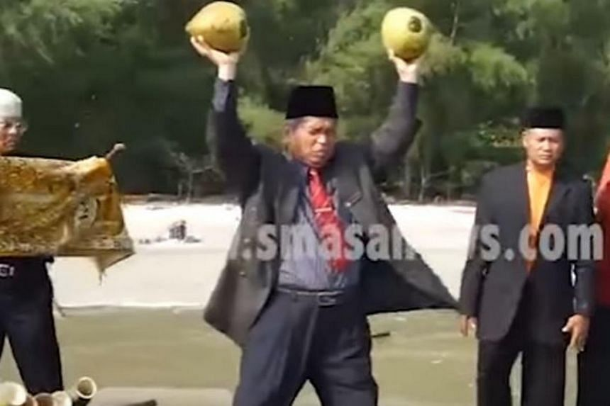 Ibrahim Mat Zin, also known as Raja Bomoh Sedunia Nujum VIP, is seen conducting the ritual with two coconuts, a pair of sticks used as binoculars, five bamboo cannons, a carpet, and a bowl of seawater.