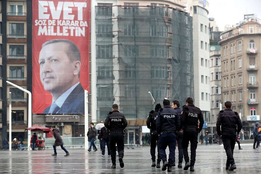 People walk in front of a giant poster of Turkish President Recep Tayyip Erdogan reading 'Vote Yes, only public can speak and make a decision' at Taksim Square in Istanbul, Turkey on March 14, 2017.