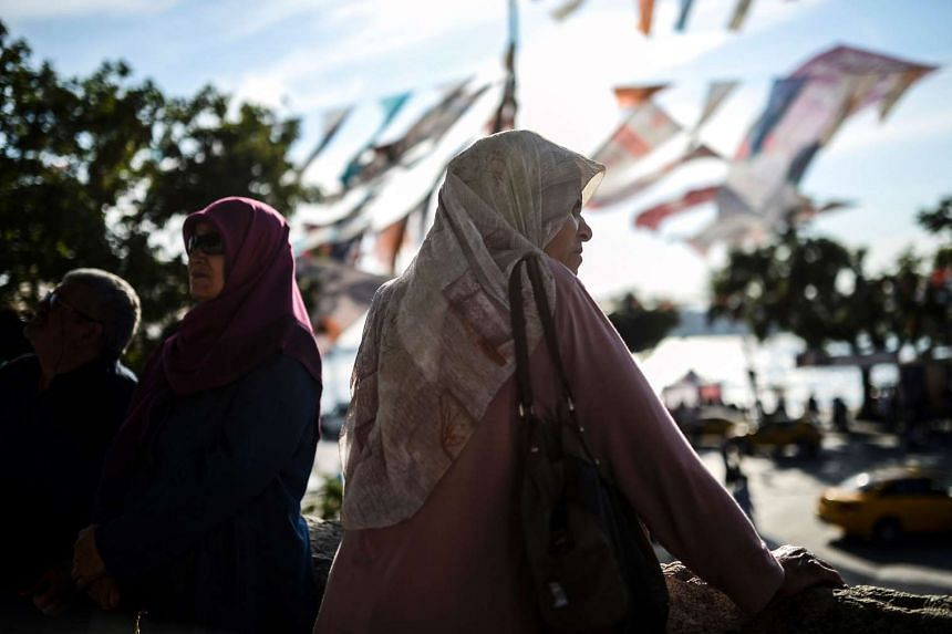 A woman wears a headscarf stands at Uskudar, in Istanbul in 2015.