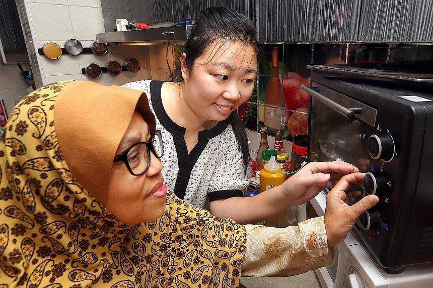During one of her home therapy sessions, NUH low-vision occupational therapist Chen Xuanyu shows Madam Ramlah Hashim, 57, how to use various household items, to help her gain confidence to live independently.