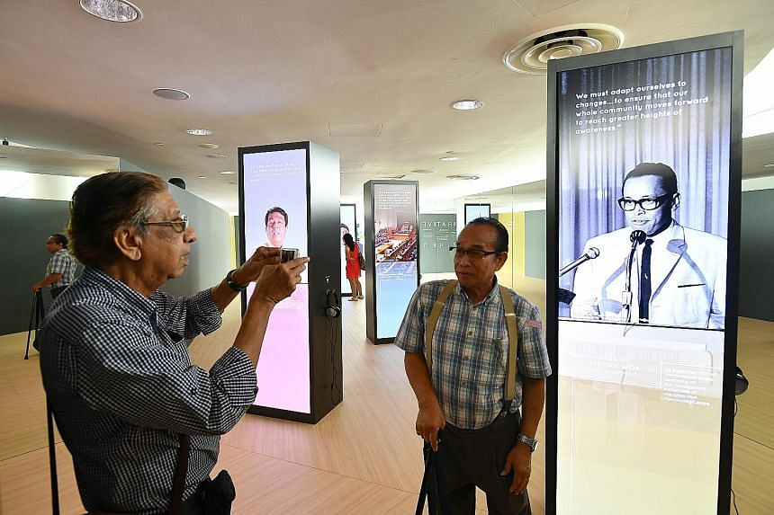 Retiree Maurice Peter Anthony, 78, taking a photograph of his friend Freddy Lim, 68, in front of the display on Mr Othman Wok at the showcase at Gardens by the Bay's Waterview Room yesterday.