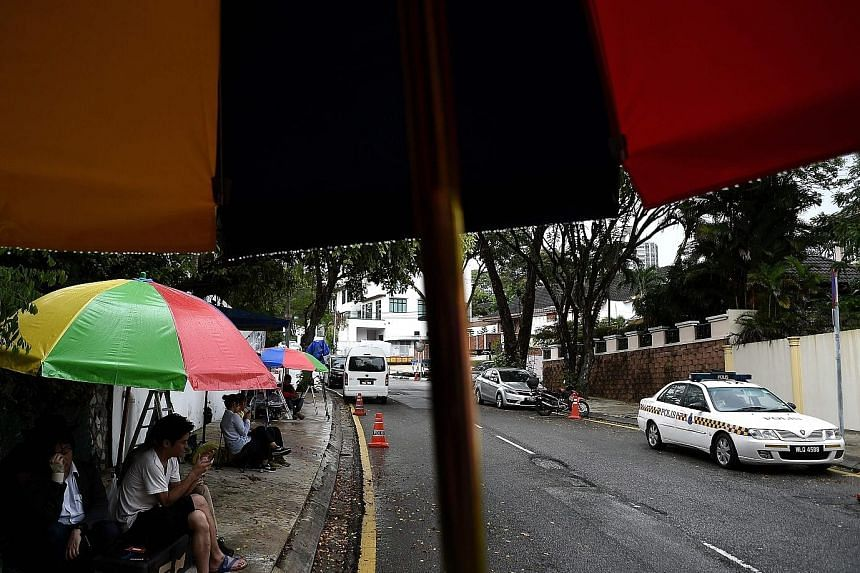 A Malaysian police car is stationed outside the North Korean Embassy in Kuala Lumpur, as journalists camp out to cover any development. A diplomat wanted by police is said to be hiding in the embassy.