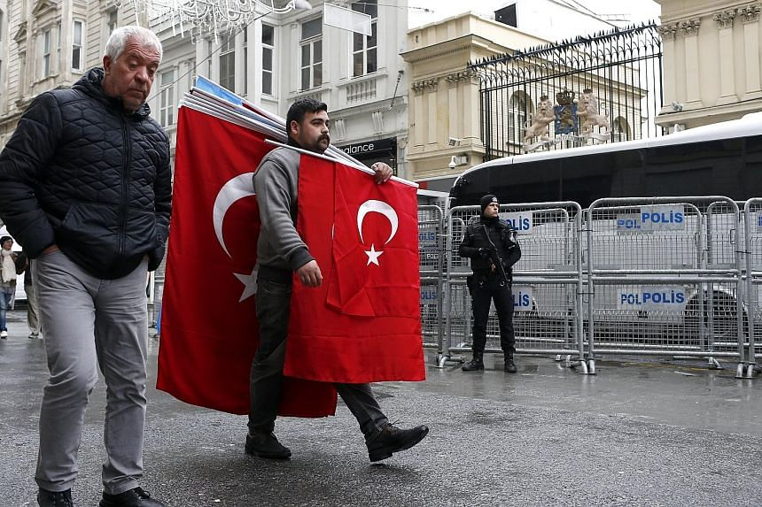 A man with Turkish flags passing a Turkish riot policeman in front of the Dutch consulate in Istanbul yesterday. Tensions between Turkey and the Netherlands escalated after a ban was enforced on Turkish ministers at political events in Rotterdam. Ank