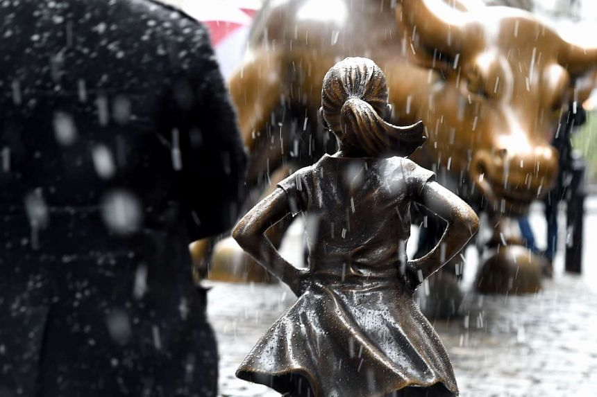 "The "" Fearless Girl "" statue on Wall Street faces off against the Wall Street bull as snow falls in New York city."
