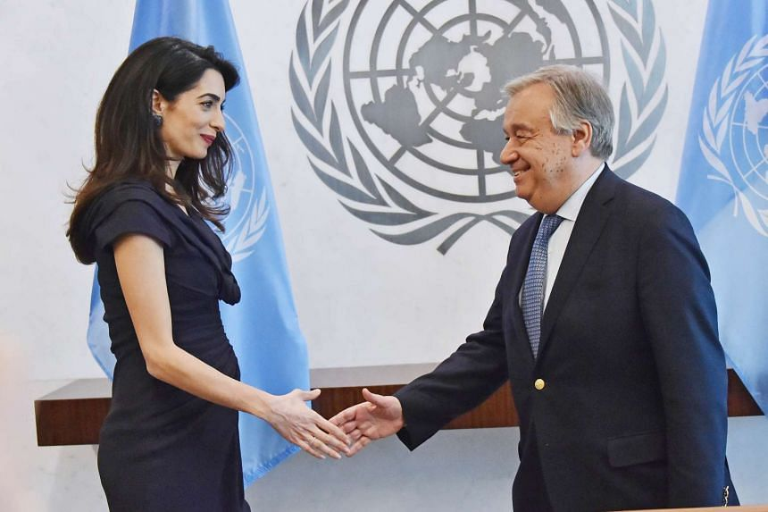 UN Secretary-General António Guterres (left) shakes hands with activist Amal Clooney at the UN in New York on March 10, 2017.