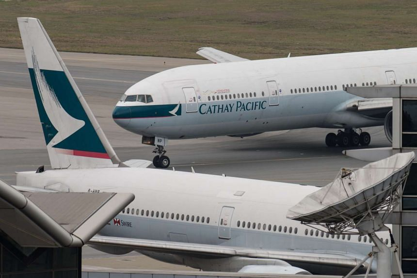 A Cathay Pacific Boeing 777 passenger aircraft (top) taxis past a stationary plane on the tarmac at the international airport in Hong Kong on March 15, 2017.