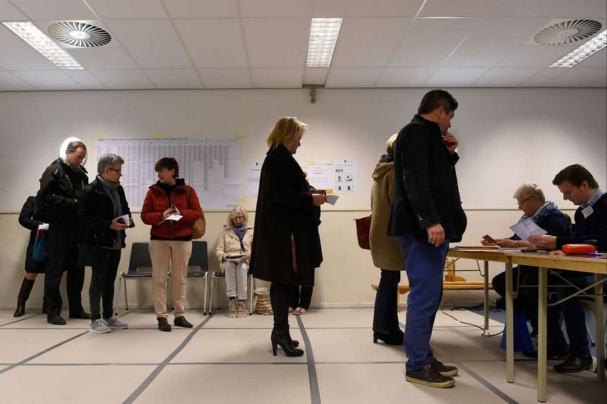 People line up to vote as polling stations open for the general elections in The Hague on March 15, 2017.