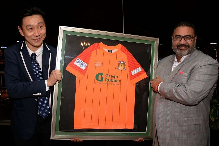 Hougang United chairman Bill Ng and Green Rubber Group chairman Vinod Sekhar displaying a new kit after signing an extension to the sponsorship deal at the club on Feb 15, 2017.