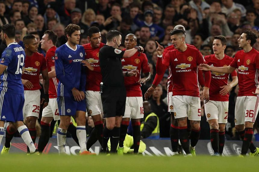 Manchester United's Marcos Rojo and teammates remonstrate with referee Michael Oliver after Ander Herrera was shown a red card.