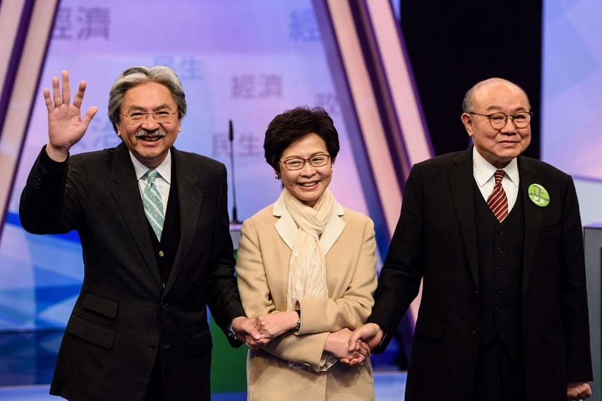 Hong Kong's three leadership candidates (from left) John Tsang, Carrie Lam and ex-judge Woo Kwok Hing joining hands as they arrive at a studio before facing off in their first televised debate in Hong Kong on March 14, 2017.