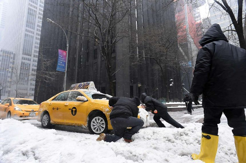 Men try to push a cab stuck in the snow on a street in New York on March 14, 2017.