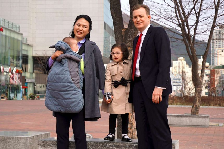 Professor Robert Kelly, his wife Kim Jung A and children Marion and James (in carrier) posing at Pusan National University in Busan on March 15, 2017.