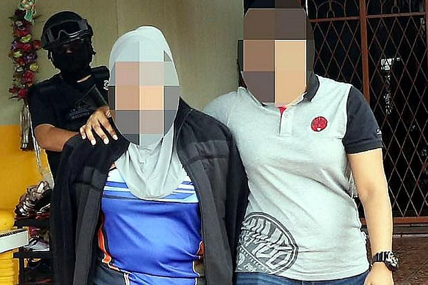Counter-terrorism officers of the Royal Malaysian Police escorting the immigration officer (in jacket) in Sandakan. As of now, she is known to have let three ISIS militants enter Malaysia in return for cash.