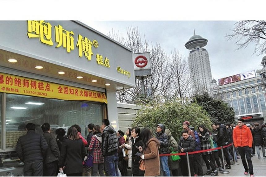 People wait in a line to buy buns of Master Bao at its first Shanghai outlet in People's Square.