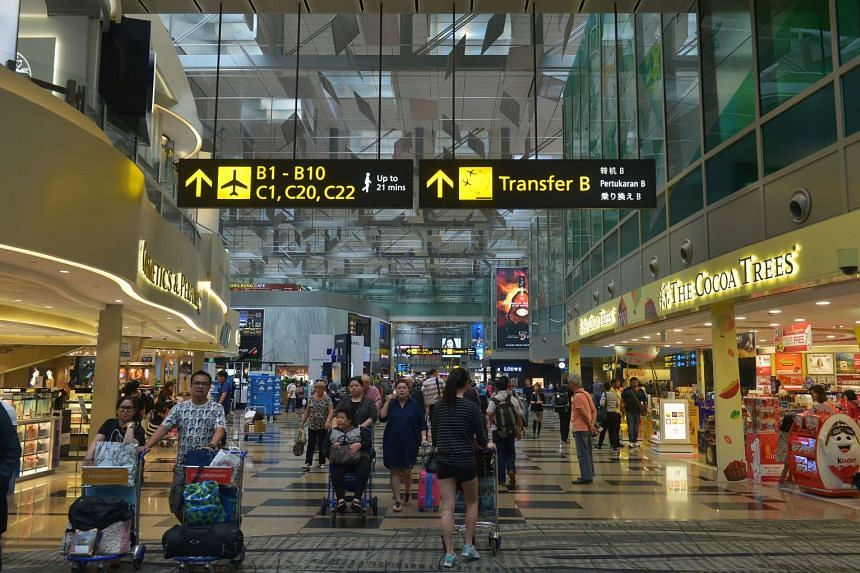 Travellers moving through the duty free shopping area in the transit lounge at Changi Airport Terminal 3.
