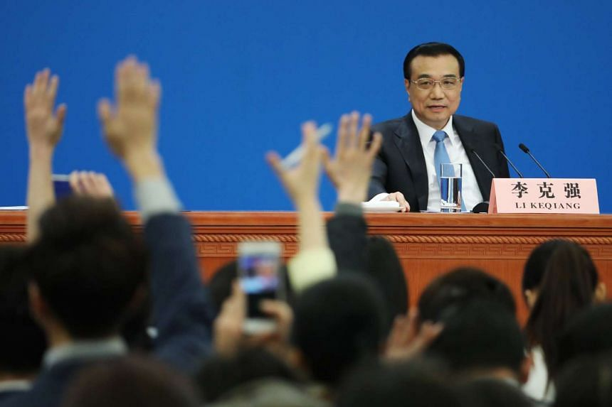 Chinese Premier Li Keqiang looking on as reporters raise their hands to ask questions during a press conference after the closing of the fifth Session of the 12th National People's Congress (NPC), on March 15, 2017.