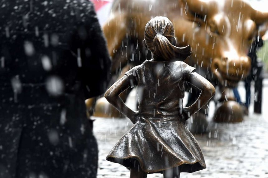 """The bronze sculpture of a young girl stands in direct challenge to Wall Street's iconic """"Charging Bull"""". It was installed on the eve of International Women's Day to promote boardroom diversity for women."""
