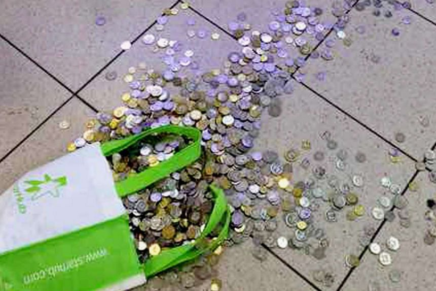 The spilt bag of coins on the floor at the mobile phone shop.