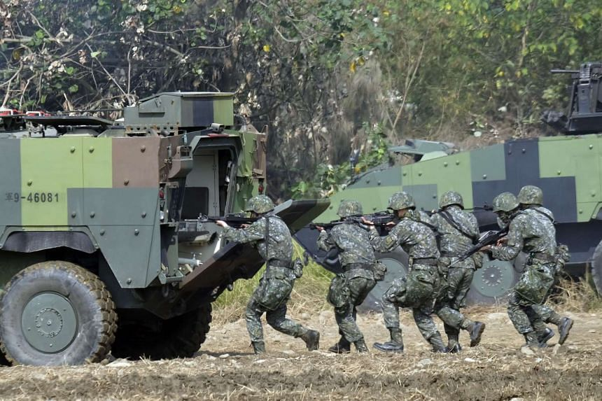 Taiwan special forces personnel walk behind an armoured personnel carrier during an annual military drill in Taichung, Taiwan.
