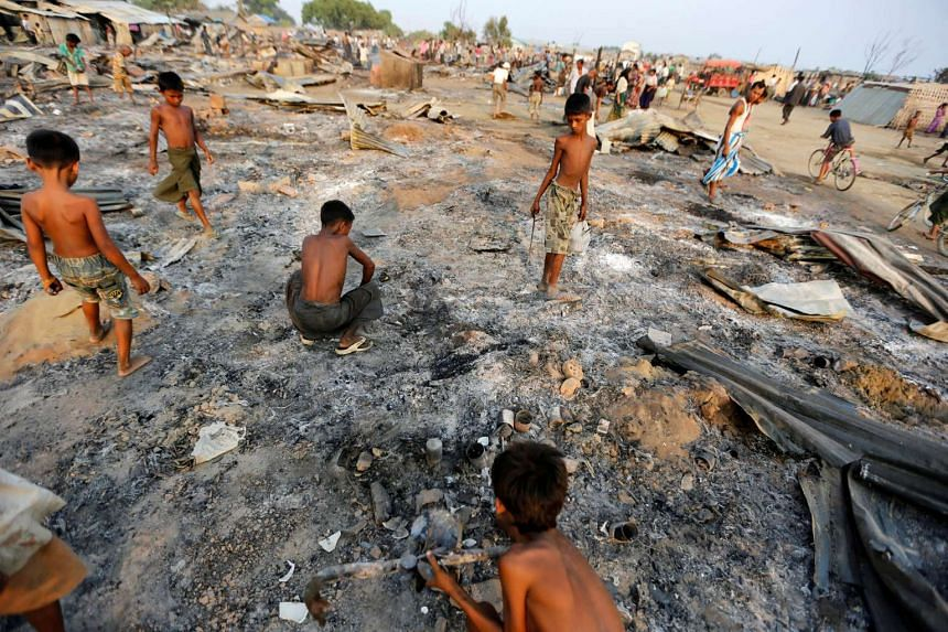 Boys search for useful items among the ashes of burnt houses after fire destroyed shelters at a camp for internally displaced Rohingya Muslims in the western Rakhine State near Sittwe, Myanmar on May 3, 2016.