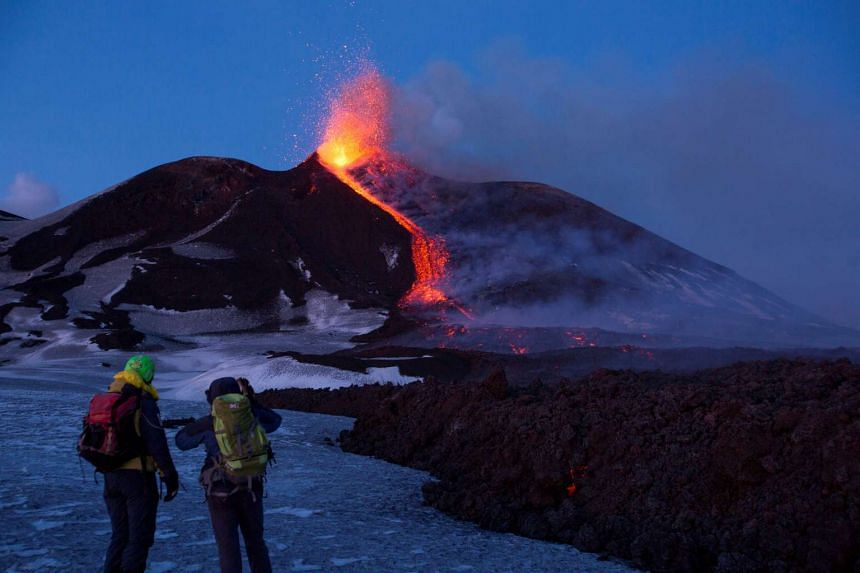Volcano guides stand in front of Italy's Mount Etna as it spews lava, Feb 28, 2017.