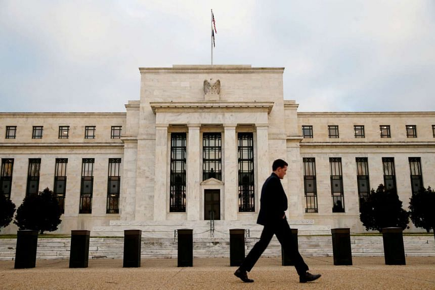 A man walking past the Federal Reserve Bank in Washington, D.C., US.