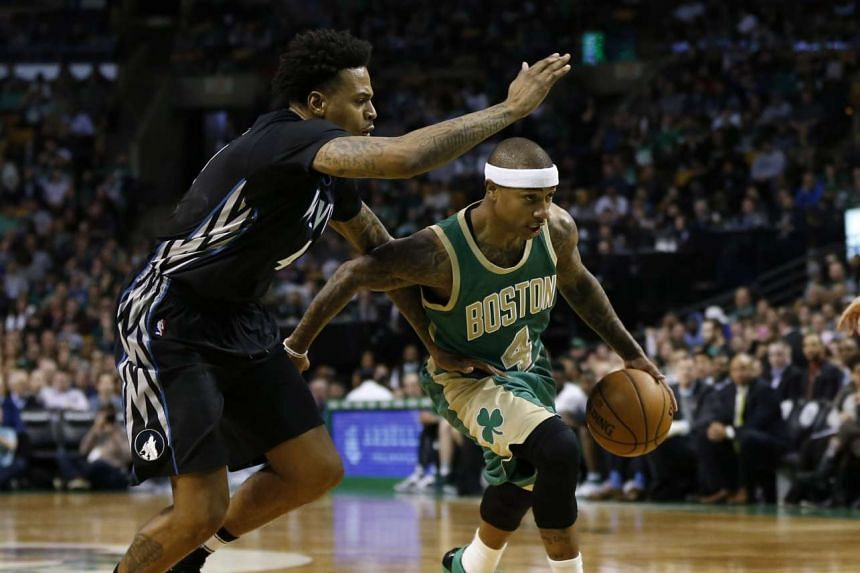Boston Celtics guard Isaiah Thomas (right) driving against Minnesota Timberwolves guard Brandon Rush during their NBA game on March 15, 2017.