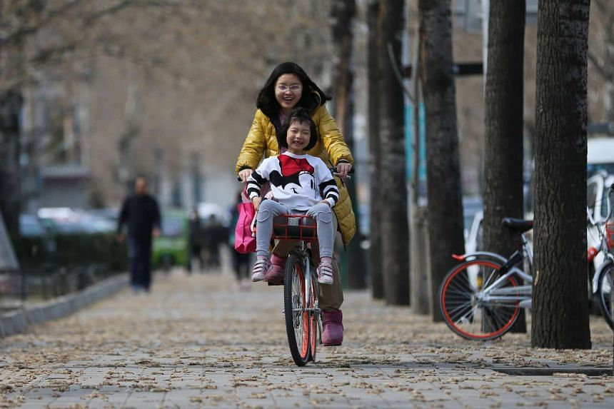 A woman rides a bicycle with her child outside the Ritan Park in Beijing, on March 11, 2017.