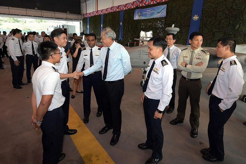 """Dr Ng Eng Hen greeting Lieutenant Marcus Chia yesterday. Looking on are (from left) Lieutenant Kidmann Goh, Major John Samuel and Chief of Air Force Mervyn Tan. Behind them is a Heron 1. Dr Ng said the use of NSFs as UAV pilots is a """"significant firs"""